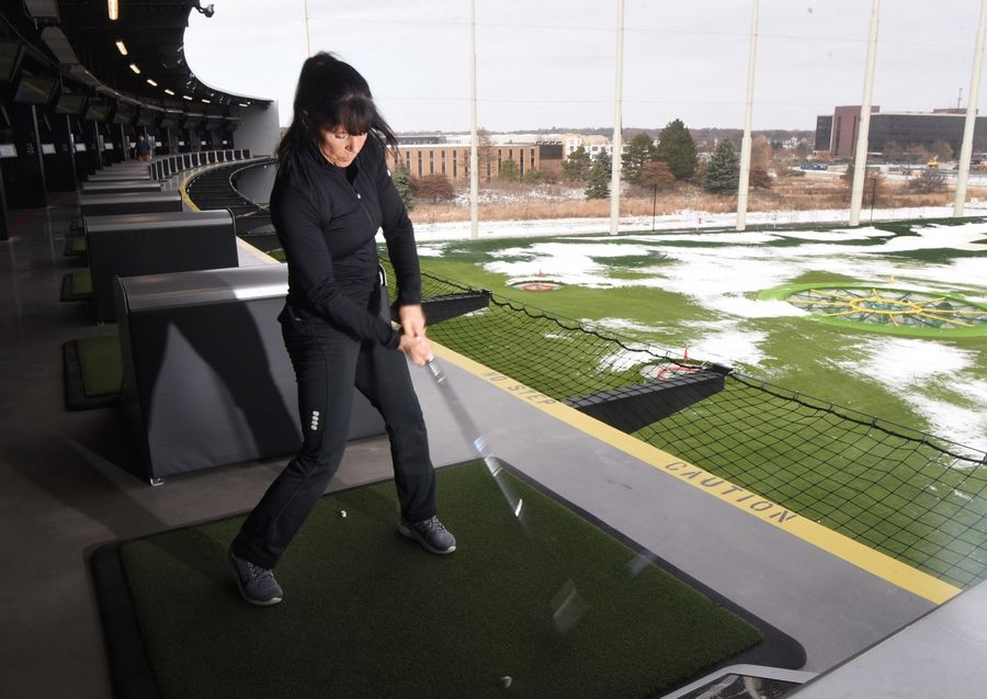 Suzi Sullivan of North Barrington hits a ball on the third level during the first official day of operation for Topgolf on the former Motorola corporate campus in Schaumburg Friday.