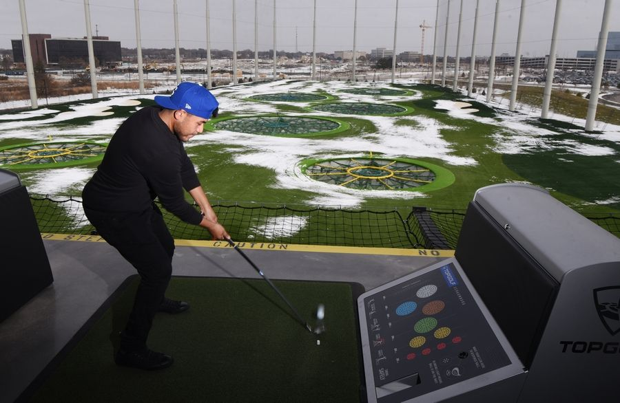 Jay Meza of Chicago hits a ball during the first official day of operation for Topgolf on the former Motorola corporate campus in Schaumburg Friday.