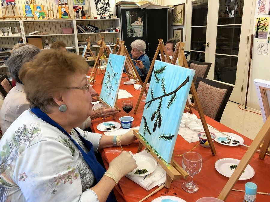 Women at Lake Barrington Woods enjoy a painting class. The senior living community in Lake Barrington organizes a range of activities for residents.
