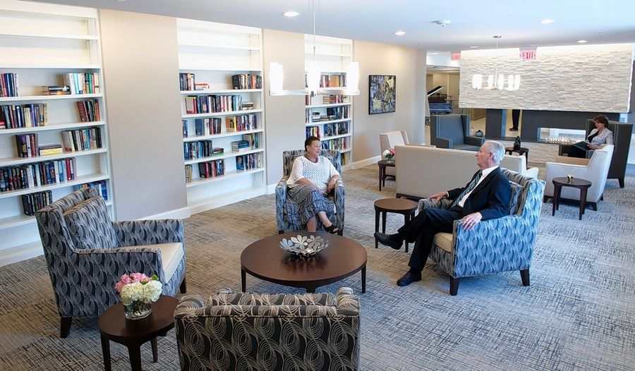 The library at The Grand at Twin Lakes offers games, book borrowing, a fireplace with stone surround and many comfortable spots to gather with friends and family.