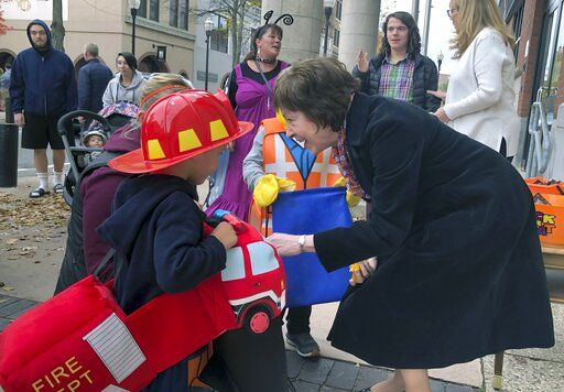 In this Friday, Oct. 25, 2019 photo, Sen. Susan Collins, R-Maine, hands out candy to children outside her office during a trick-or-treat event hosted by the local chamber of commerce in Lewiston, Maine. Collins is expected to make a formal announcement on her reelection plans later this fall.