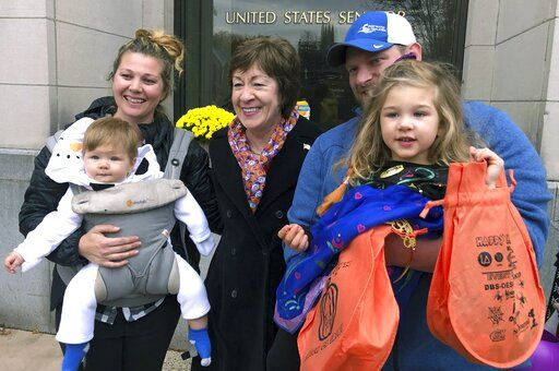 In this Friday, Oct. 25, 2019 photo, Sen. Susan Collins, R-Maine, poses with citizens for a photo outside her office during a tricks-or-treat event hosted by the local chamber of commerce in Lewiston, Maine. Collins is expected to make a formal announcement on her reelection plans later this fall.