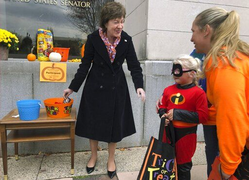 In this Friday, Oct. 25, 2019 photo, Sen. Susan Collins, R-Maine, hands out candy to children outside her office during a tricks-or-treat event hosted by the local chamber of commerce in Lewiston, Maine. Collins is expected to make a formal announcement on her reelection plans later this fall.