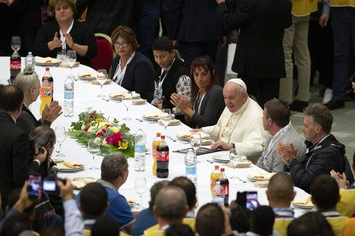 Pope Francis sits at a table during a lunch, in the Paul VI Hall at the Vatican, Sunday, Nov. 17, 2019. Pope Francis is offering several hundred poor people, homeless, migrants, unemployed a lunch on Sunday as he celebrates the World Day of the Poor with a concrete gesture of charity in the spirit of his namesake, St. Francis of Assisi.