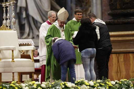 A family walks on the altar during the offertory of a Mass celebrated by Pope Francis in St. Peter Basilica at the Vatican, Sunday, Nov. 17, 2019. Pope Francis is offering several hundred poor people, homeless, migrants, unemployed a lunch on Sunday as he celebrates the World Day of the Poor with a concrete gesture of charity in the spirit of his namesake, St. Francis of Assisi, Sunday, Nov. 17, 2019.