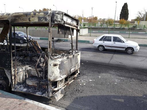 "This photo released by the Iranian Students' News Agency, ISNA, shows cars drive past a scorched public bus that remained on the street after protests that followed authorities' decision to raise gasoline prices, in Tehran, Iran, Sunday, Nov. 17, 2019.  Ayatollah Ali Khamenei, Iran's supreme leader, on Sunday backed the government's decision to raise gasoline prices and called angry protesters who have been setting fire to public property over the hike ""thugs,"" signaling a potential crackdown on the demonstrations. (Morteza Zangane/ISNA via AP)"