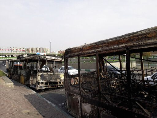 "This photo released by the Iranian Students' News Agency, ISNA, shows scorched public buses that remained on the street after protests that followed authorities' decision to raise gasoline prices, in Tehran, Iran, Sunday, Nov. 17, 2019.  Ayatollah Ali Khamenei, Iran's supreme leader, on Sunday backed the government's decision to raise gasoline prices and called angry protesters who have been setting fire to public property over the hike ""thugs,"" signaling a potential crackdown on the demonstrations. (Morteza Zangane/ISNA via AP)"