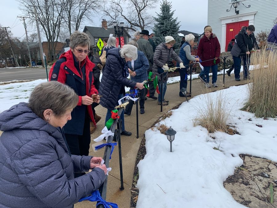 Members and friends from St. Paul UCC tie ribbons to the outdoor railings and offer prayers or wishes of peace, hope, joy and love for our world on Sunday, November 17. Steven Chwalisz