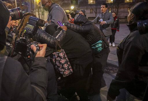 Supporters surround and hide from view one of two jail guards, center, responsible for monitoring Jeffrey Epstein the night he killed himself, following their federal court arraignment charge for falsifying prison records, Tuesday Nov. 19, 2019, in New York.