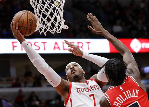 FILE - In this Nov. 3, 2018, file photo, Houston Rockets forward Carmelo Anthony, left, drives to the basket against Chicago Bulls forward Justin Holiday during the first half of an NBA basketball game in Chicago. A person familiar with the details says Anthony is returning to the NBA with the Portland Trail Blazers. The 10-time All-Star has not played since a short stint with the Rockets ended a little more than a year ago after just 10 games.