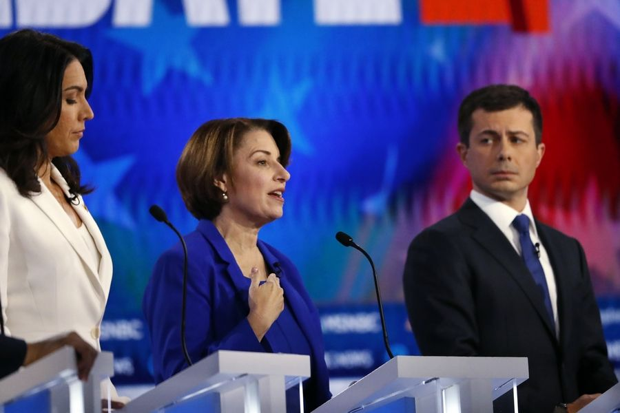 Democratic presidential candidate Sen. Amy Klobuchar of Minnesota, center, speaks Wednesday as Democratic presidential candidates Rep. Tulsi Gabbard of Hawaii, left, and South Bend, Indiana, Mayor Pete Buttigieg listen during a Democratic presidential primary debatevin Atlanta.
