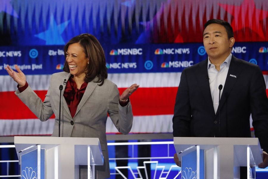 Democratic presidential candidate Sen. Kamala Harris of California reacts Wednesday while speaking as former technology executive Andrew Yang looks on during primary debate, Wednesday in Atlanta.