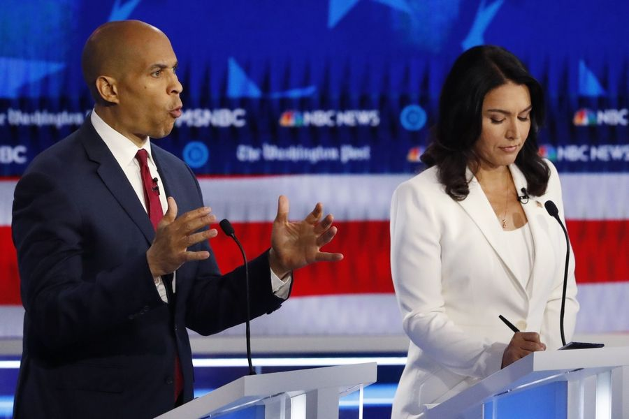 Democratic presidential candidate Sen. Cory Booker of New Jersey speaks Wednesday as Rep. Tulsi Gabbard of Hawaii listens during a presidential primary debate in Atlanta.