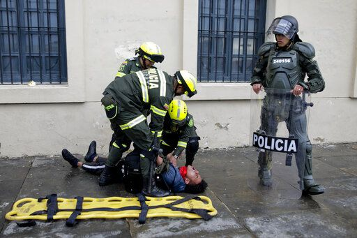 Police attend an anti-government protester affected by tear gas during clashes in downtown Bogota, Colombia, Friday, Nov. 22, 2019. Labor unions and student leaders called on Colombians to bang pots and pans Friday evening in another act of protest while authorities announced three people had died in overnight clashes with police after demonstrations during a nationwide strike.