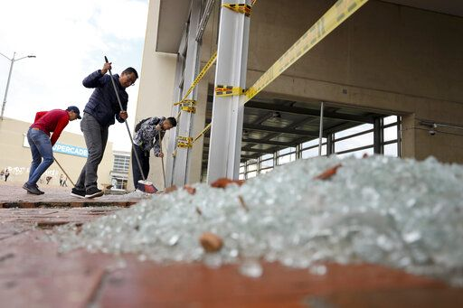 Workers clear broken glass from a bus station damaged by anti-government demonstrators, in Bogota, Colombia, Friday, Nov. 22, 2019. Protesters attacked the station Thursday during a nationwide strike called by labor unions, students and teachers to protest everything from economic inequality to violence against social leaders.