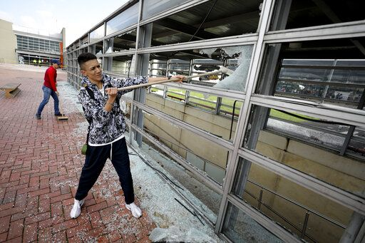 A worker clears broken glass from a bus station damaged by anti-government demonstrators, in Bogota, Colombia, Friday, Nov. 22, 2019. Protesters attacked the station Thursday during a nationwide strike called by labor unions, students and teachers to protest everything from economic inequality to violence against social leaders.