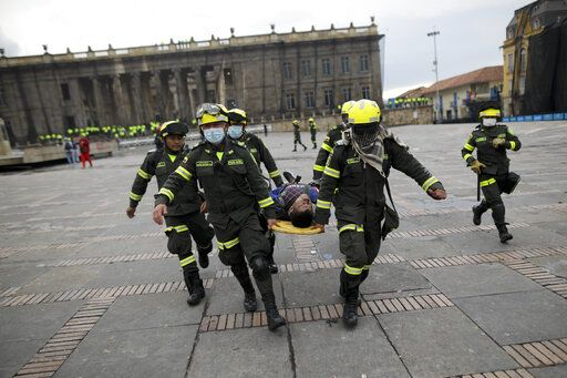 Police carry an anti-government protesters affected by tear gas after clashes at the Bolivar square in downtown Bogota, Colombia, Friday, Nov. 22, 2019. Labor unions and student leaders called on Colombians to bang pots and pans Friday evening in another act of protest while authorities announced three people had died in overnight clashes with police after demonstrations during a nationwide strike.