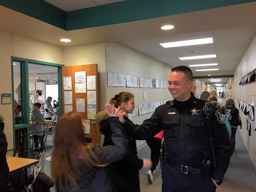 Huntley High School school resource officer Ryan Gregorio greets children last December at Leggee Elementary School in Huntley. A resolution to create funding to help school districts hire resource officers gained the support of the Illinois Association of School Boards on Saturday.