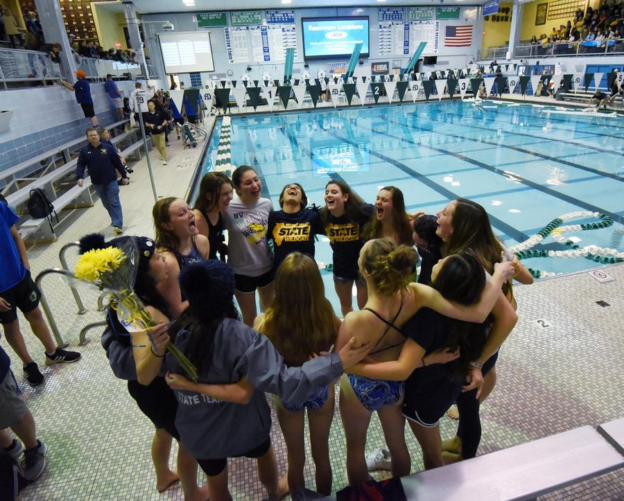The Neuqua Valley Wildcats huddle near the pool after winning the girls state swimming and diving championship at New Trier High School in Winnetka Saturday.