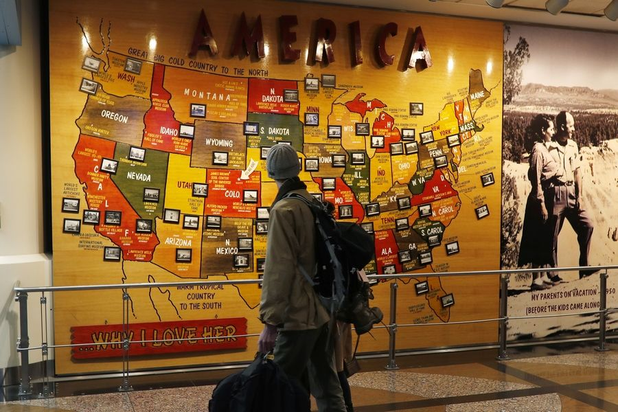 Travelers pass by a map of the United States on the way to a security checkpoint at Denver International Airport in Denver.