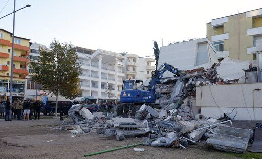People stand near a damaged building after an earthquake in Durres, western Albania, Tuesday, Nov. 26, 2019. A strong earthquake has shaken Albania, killing at least four people, injuring 150 and collapsing buildings.