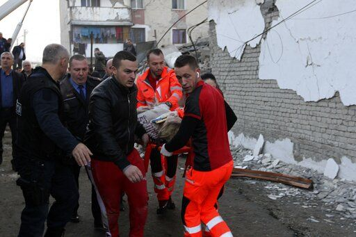 Rescuers carry an injured woman after a magnitude 6.4 earthquake in Thumane, western Albania, Tuesday, Nov. 26, 2019. Rescue crews used excavators to search for survivors trapped in toppled apartment buildings after a powerful pre-dawn earthquake in Albania killed at least six people and injured more than 300.