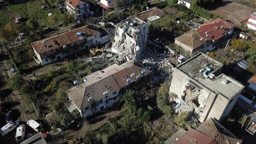 Rescuers search at a damaged building after a magnitude 6.4 earthquake in Thumane, western Albania, Tuesday, Nov. 26, 2019. Rescue crews used excavators to search for survivors trapped in toppled apartment buildings Tuesday after a powerful pre-dawn earthquake in Albania killed at least 14 people and injured more than 600.