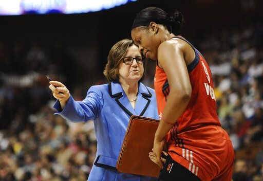 FILE - In this Aug. 10, 2014, file photo, Washington Mystics' assistant coach Marianne Stanley, left, talks with player Kia Vaughn during the first half of a WNBA basketball game, in Uncasville, Conn. The Indiana Fever has hired Marianne Stanley as its new head coach. Stanley had been an assistant with the Washington Mystics since 2010 and was part of last season's WNBA championship run. She was named the 2002 WNBA coach of the year with Washington and has served as an assistant with the Los Angeles Sparks and New York Liberty.