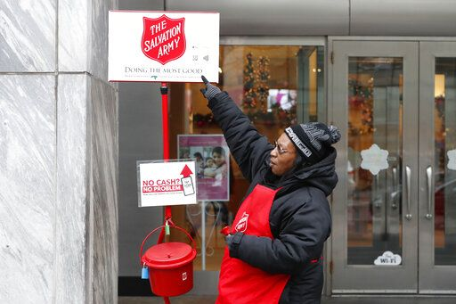In this Friday, Nov. 15, 2019, photo, bell ringer Carolyn Harper points to two ways to donate via mobile device to the Salvation Army's annual holiday red kettle campaign on Chicago's Magnificent Mile. Cashless shoppers have a new option to give to the Army's red kettle campaign this year using their smartphone. Leaders hope adding Apple and Google payment options will boost fundraising to the campaign, which makes up 10% of The Salvation Army's annual budget. Those donations fund programs providing housing, food and other support to people in poverty.