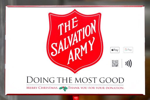 In this Friday, Nov. 15, 2019, photo, two ways to donate via Apple Pay and Google Pay to the Salvation Army's annual holiday red kettle campaign are incorporated next to the Army's iconic red shield on Chicago's Magnificent Mile. Cashless shoppers have a new option to give to the Army's red kettle campaign this year using their smartphone. Leaders hope adding Apple and Google payment options will boost fundraising to the campaign, which makes up 10% of The Salvation Army's annual budget. Those donations fund programs providing housing, food and other support to people in poverty.