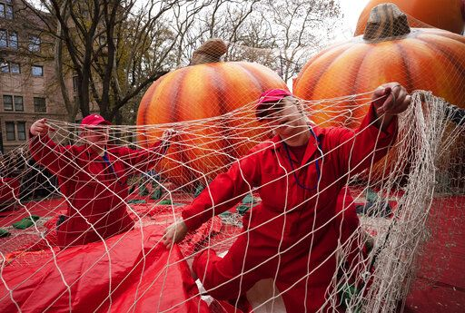 Michele Schleibaum, right, arranges protective netting on the Power Rangers Mighty Morphin Red Ranger balloon as it is inflated, Wednesday, Nov. 27, 2019 in New York. The netting will be in place overnight. New York City's big Macy's Thanksgiving Day Parade on Thursday will take place amid strong winds that could potentially ground the giant character balloons.