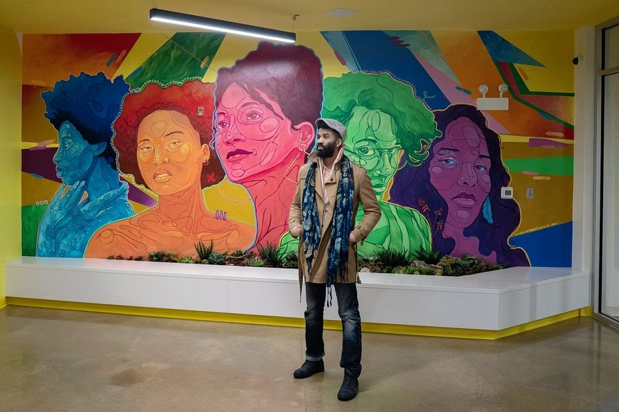 Artist David Anthony Geary stands in front of his mural of creative Chicago women in the front lobby of KLEO Art Residences in Chicago.