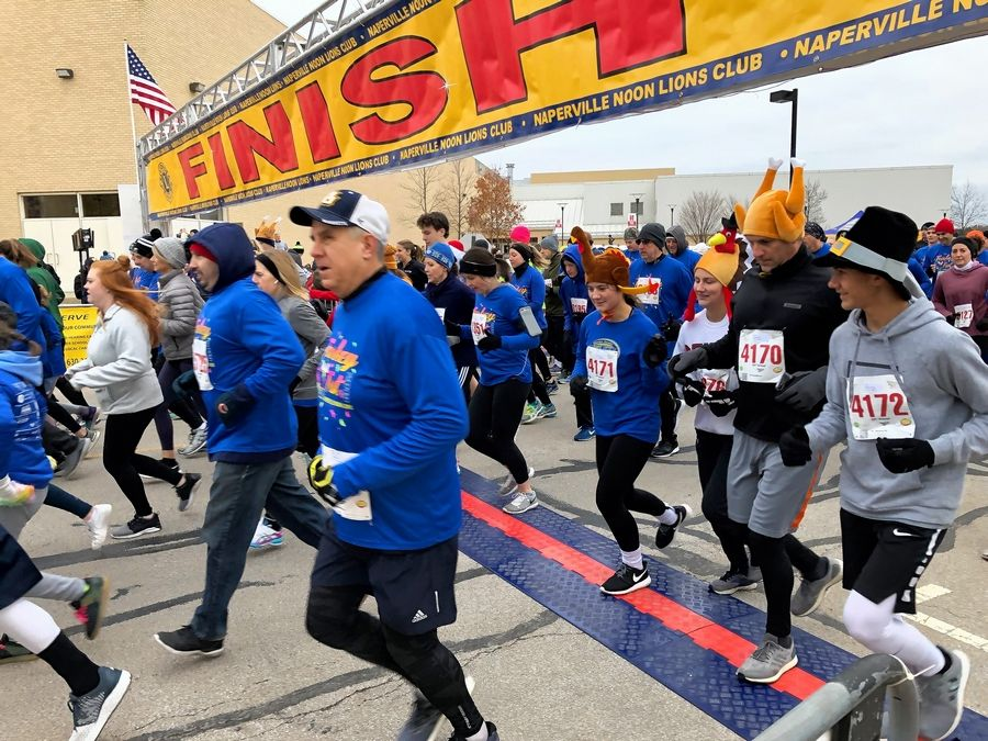 Runners step off from the start/finish line at the Naperville Turkey Trot Thanksgiving morning.