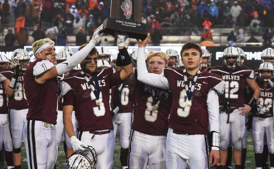 Prairie Ridge captains, from left, Andrew Fryer, Blake Brown, Kyle Koelblinger and Connor Lydon hold their team's trophy following the Wolves' 43-21 loss to East St. Louis during the IHSA Class 6A state football title game at Northern Illinois University in DeKalb Saturday.
