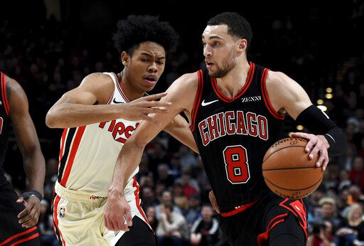 Chicago Bulls guard Zach LaVine, right, drives to the basket on Portland Trail Blazers guard Anfernee Simons during the first quarter of an NBA basketball game in Portland, Ore., Friday, Nov. 29, 2019.