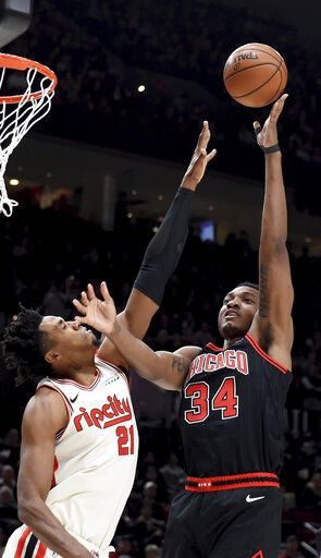 Chicago Bulls center Wendell Carter Jr., right, shoots the ball over Portland Trail Blazers center Hassan Whiteside during the first quarter of an NBA basketball game in Portland, Ore., Friday, Nov. 29, 2019.