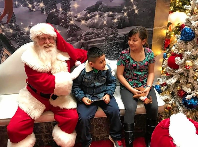 Santa poses for a picture with Vinny Aguayo- Lopez of Waukegan and his sister, Jennifer, on Sunday during the Soothing Santa event at Hawthorn Mall in Vernon Hills.