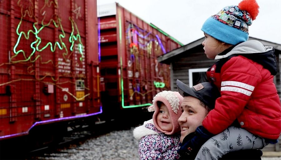 Zach Russavage of Lombard on Monday smiles at the Holiday Train with his children Sully, 4, and Cici, 2 in Bensenville. For the second year, Bensenville was visited Monday by the Canadian Pacific Rail Holiday Train.