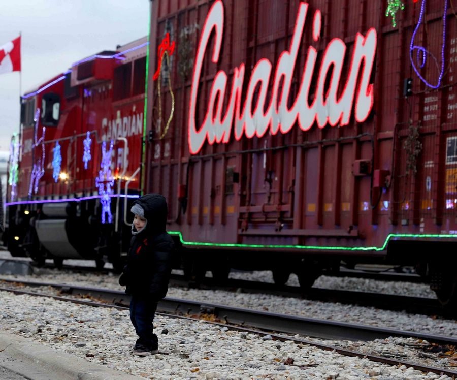 Anthony Lonero, 2, of Wood Dale smiles as he has his picture taken by his mother Paula on Monday in Bensenville. For the second year, Bensenville was visited by the Canadian Pacific Rail Holiday Train.