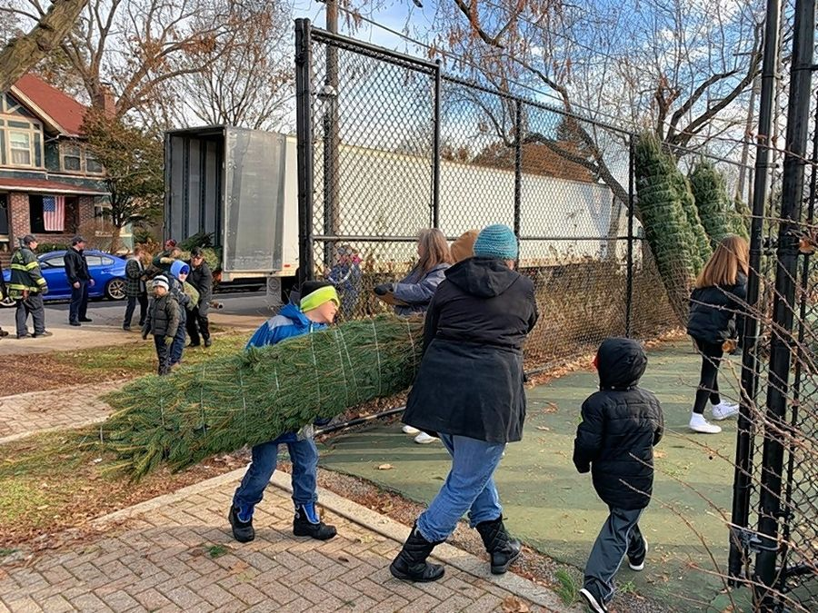 Community volunteers help unload the Christmas trees for the Dundee Lions Club annual fundraiser. Lions Clubs and Boy Scout Troops around the Fox Valley are hosting Christmas tree sales.