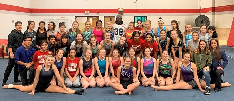Kerrith Whyte of the Chicago Bears with the Mundelein High School gymnastics team. Whyte toured the facilities at the high school and spent time with some of the athletic teams while on hand to assist with collecting and sorting items for the new District 120 Welcome Center.