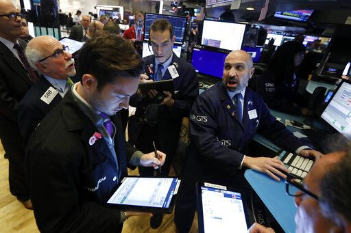 FILE - In this Nov. 14, 2019, file photo specialist James Denaro, right, works with traders at his post on the floor of the New York Stock Exchange. The U.S. stock market opens at 9:30 a.m. EST on Monday, Dec. 2.