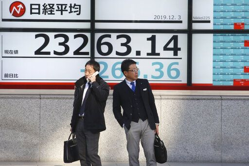 People stand in front of an electronic stock board of a securities firm in Tokyo, Tuesday, Dec. 3, 2019. Asian shares slipped Tuesday, following a drop on Wall Street amid pessimism over U.S.-China trade tensions.