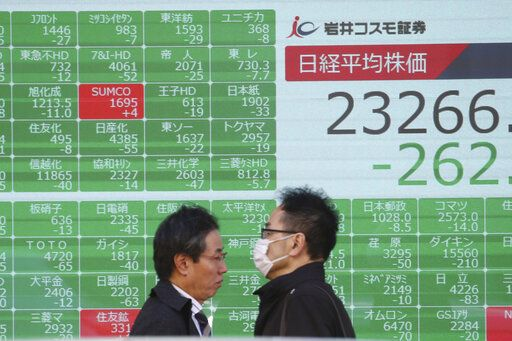 People walk by an electronic stock board of a securities firm in Tokyo, Tuesday, Dec. 3, 2019. Asian shares slipped Tuesday, following a drop on Wall Street amid pessimism over U.S.-China trade tensions.