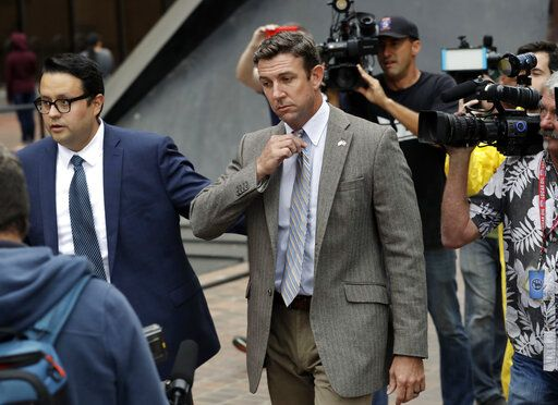 CORRECTS TO ATTRIBUTE THE REFERENCE TO HUNTER, NOT A JUSGE - FILE - In this Sept. 24, 2018, file photo, U.S. Rep. Duncan Hunter, center, leaves court in San Diego. The California Republican plans to plead guilty on Tuesday, Dec. 3, 2019, to the misuse of campaign funds and has indicated he will leave Congress, he told KUSI television in San Diego in an interview that aired Monday.