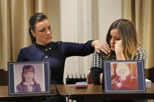 Teresa Forteny-Miller, left, comforts her sister Carolyn Fortney as they sit behind pictures of themselves as children as they listen to their other sisters speak during a news conference in Newark, N.J., Monday, Dec. 2, 2019. Two of the sisters from Pennsylvania are suing the Archdiocese of Newark and the Diocese of Harrisburg, Pennsylvania. They allege clergy in Newark knew a priest had sexually abused children before he moved to Harrisburg and abused them and their sisters for years. Lawsuits alleging sexual abuse by Roman Catholic clergy are taking center stage in New Jersey as the state's relaxation of statute of limitations rules takes effect.