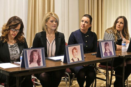 Sisters Patty Fortney-Julius, Lara Fortney McKeever, second from left, Teresa Forteny-Miller, second from right, and Carolyn Fortney sit behind pictures of themselves as children as they listen to an attorney speak to reporters during a news conference in Newark, N.J., Monday, Dec. 2, 2019. Two of the sisters from Pennsylvania, Patty and Lara, are suing the Archdiocese of Newark and the Diocese of Harrisburg, Pennsylvania. They allege clergy in Newark knew a priest had sexually abused children before he moved to Harrisburg and abused them and their sisters for years. Lawsuits alleging sexual abuse by Roman Catholic clergy are taking center stage in New Jersey as the state's relaxation of statute of limitations rules takes effect.