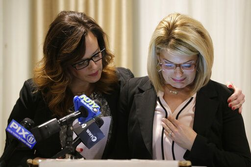As Patty Fortney-Julius, left, offers support, her sister Lara Fortney McKeever cries as she speaks to reporters during a news conference in Newark, N.J., Monday, Dec. 2, 2019. The two sisters from Pennsylvania are suing the Archdiocese of Newark and the Diocese of Harrisburg, Pennsylvania. They allege clergy in Newark knew a priest had sexually abused children before he moved to Harrisburg and abused them and their sisters for years. Lawsuits alleging sexual abuse by Roman Catholic clergy are taking center stage in New Jersey as the state's relaxation of statute of limitations rules takes effect.