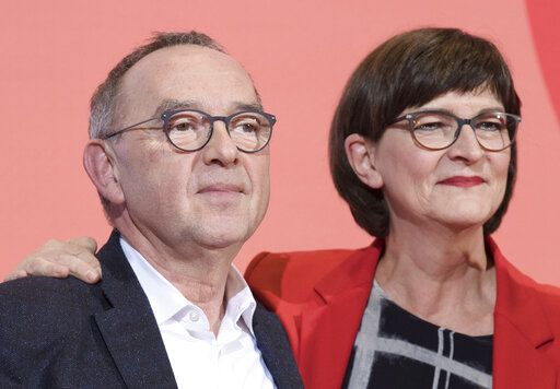 Norbert Walter-Borjans, left, and Saskia Esken stand on the podium after winning the member voting of the Social Democratic Party, SPD, chairmanship at the party's headquarters in Berlin, Germany, Saturday, Nov. 30, 2019. Norbert Walter-Borjans and Saskia Esken beat the rival team of Vice Chancellor Olaf Scholz and Klara Geywitz in a runoff ballot of the Social Democrats' members, according to results announced Saturday. (Joerg Carstensen/dpa via AP)