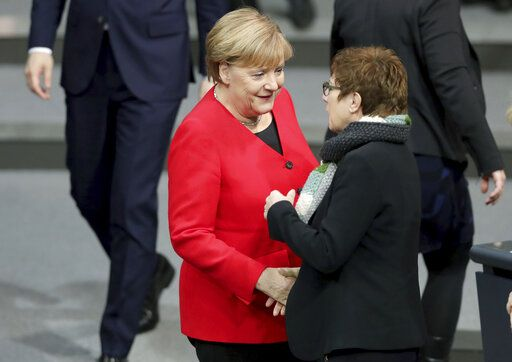 German Chancellor Angela Merkel, left, and Annegret Kramp-Karrenbauer, right, Defence Minister and chairwoman of the German Christian Democratic Union CDU, shake hands as they arrive for a meeting of the German federal parliament, Bundestag, at the Reichstag building in Berlin, Germany, Wednesday, Nov. 27, 2019.